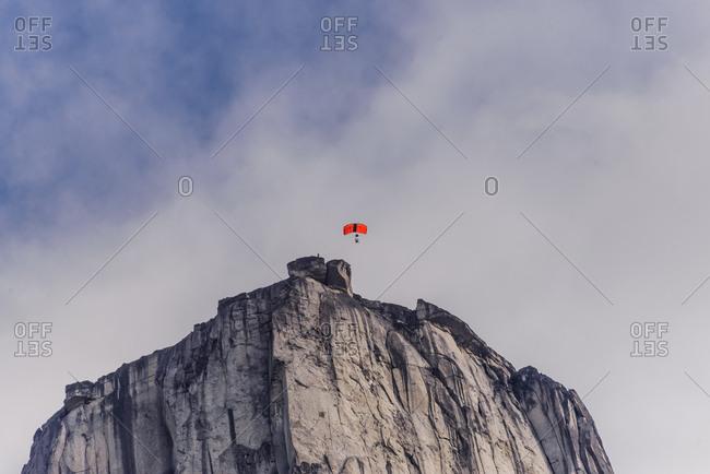 Person paragliding from mountain in the Tasermiut Fjord, Narsaq, Vestgronland, Greenland