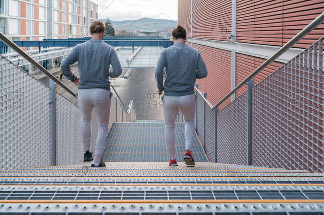 Young adult male twins running together, running down city stairway, rear view