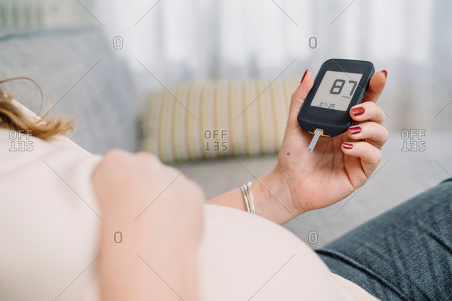 Pregnant woman on sofa looking at blood sugar test, cropped