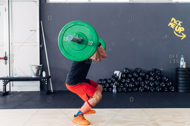 Side view of man weightlifting barbell in gym