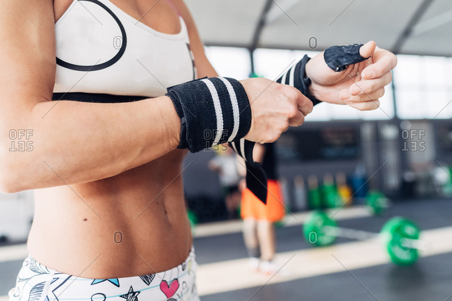 Cropped view of woman preparing for weightlifting, wearing gym gloves