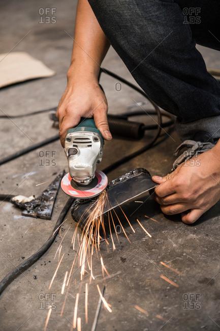 Mechanic working at custom motorbike shop, Bangkok, Thailand