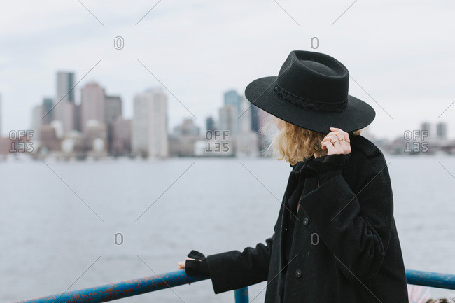 Woman wearing hat looking away at skyline, Boston, Massachusetts, United States