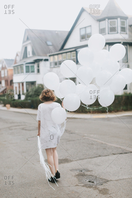 Woman in street holding bunch of balloons, rear view, Boston, Massachusetts, United States