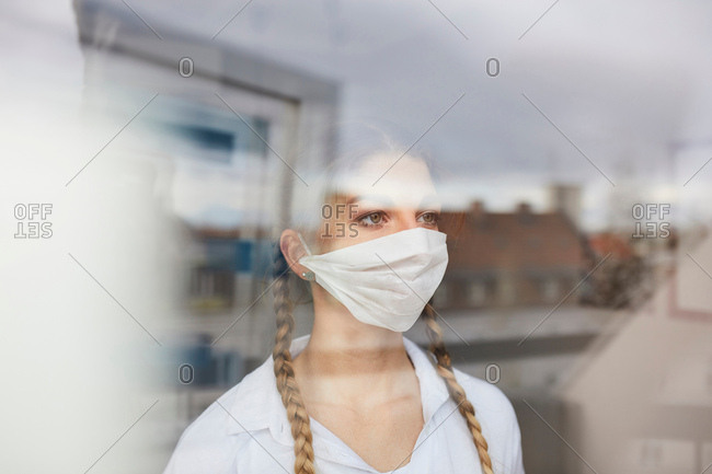 Young female doctor in surgical mask looking out of hospital window