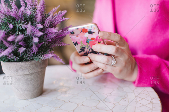 Young woman sitting at table using smartphone,  close up