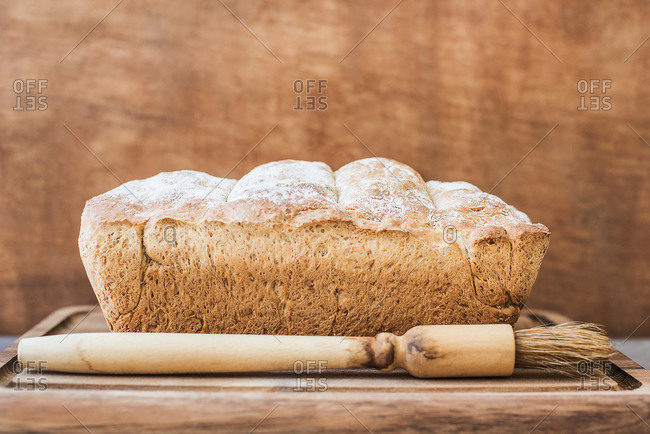 Freshly baked loaf of whole wheat bread on wooden surface