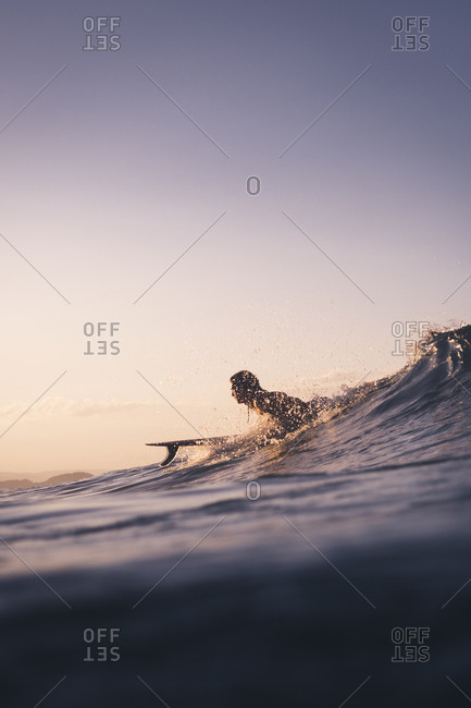 Surfer lying on surfboard while wave is forming and water splashing
