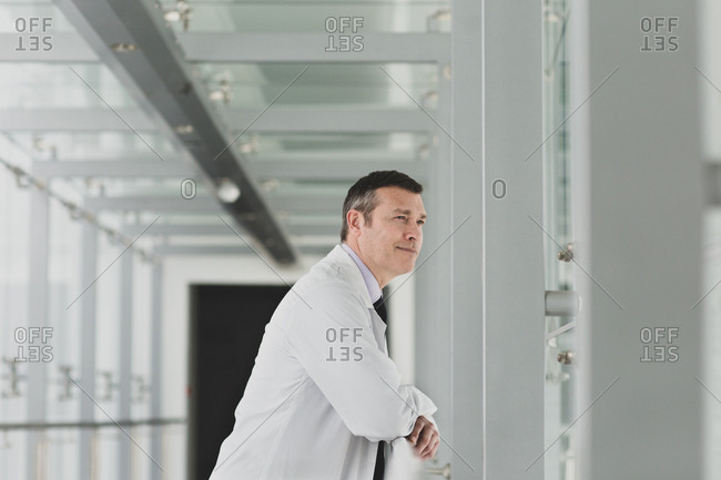 Healthcare professional looking out of window in a modern hospital