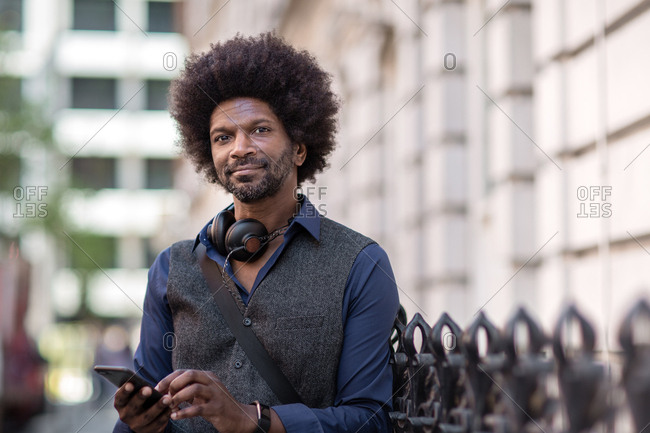 Portrait of African American male outdoors with smartphone