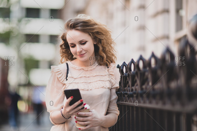 Young adult female looking at smartphone outdoors in city