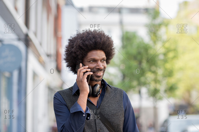 African American male walking and on  smartphone in city