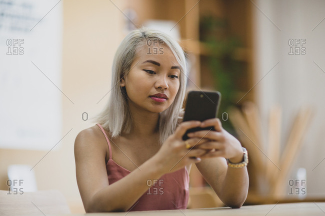 Young adult female using smartphone in college