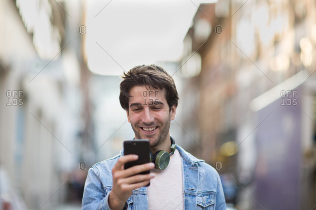 Young adult male laughing at smartphone