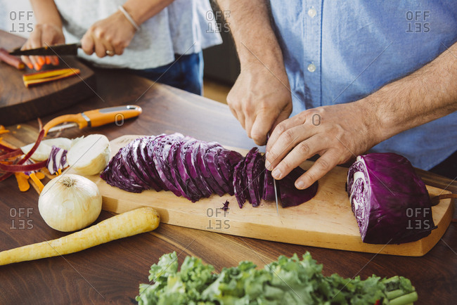 Cropped image of man cutting cabbage on board in kitchen