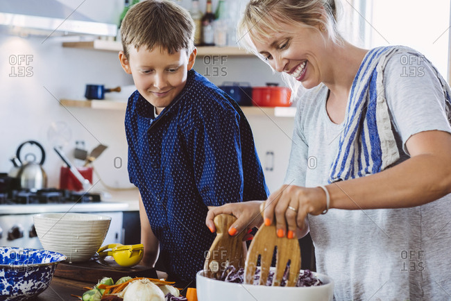Little boy looking at mother mixing salad in bowl while standing at kitchen island