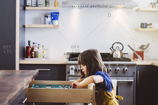 Side view of little girl arranging utensils in drawer in kitchen