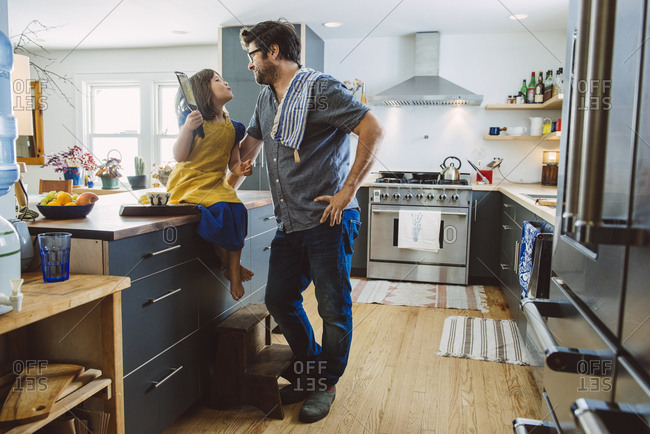 Full length of mature father looking at daughter sitting on kitchen island at home