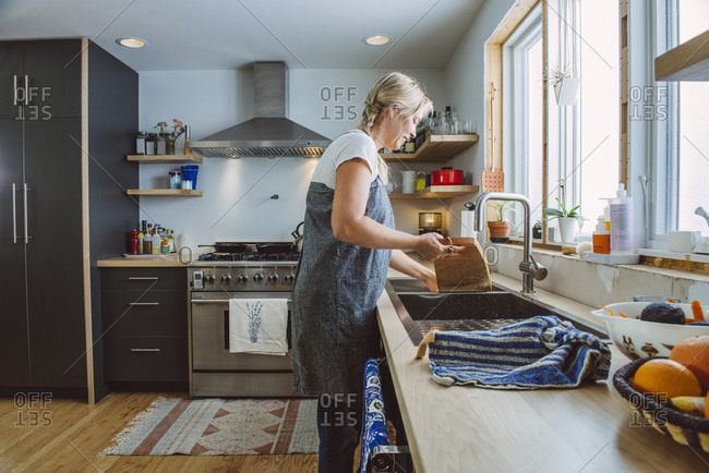 Side view of mid adult woman washing cutting board while standing in kitchen