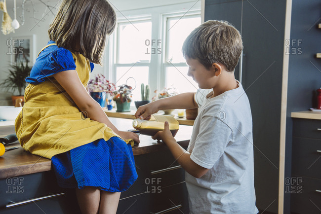 Brother and sister cooking in kitchen together