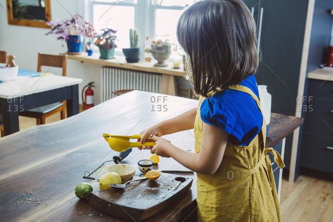 Little girl juicing lemon while standing at kitchen island