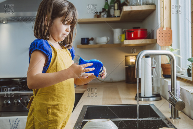Cute little girl washing dishes at kitchen sink