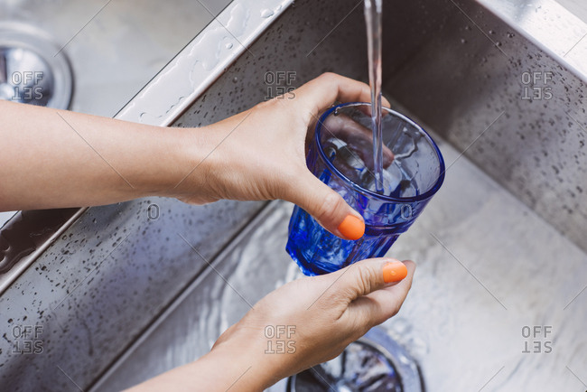 Closeup of woman's hands washing glass in kitchen sink
