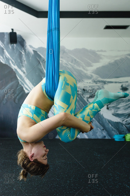 Beautiful fit woman practicing aerial yoga in the gym