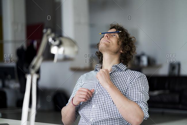 Businessman balancing pencil on his face