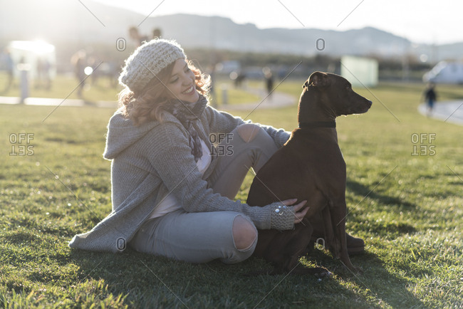 Happy young woman sitting on a meadow with her dog