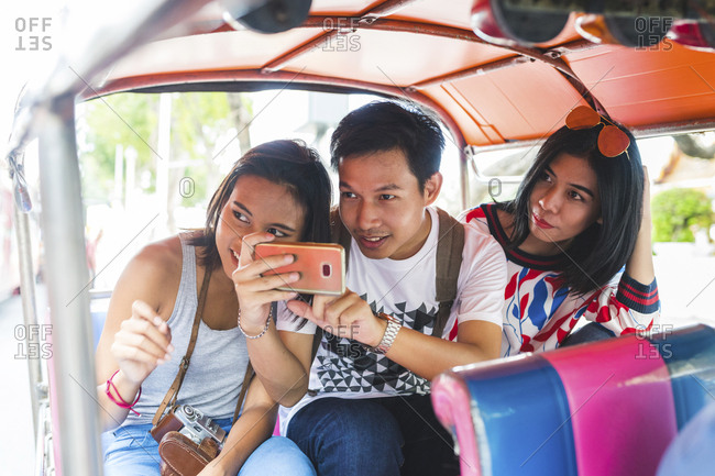 Thailand- Bangkok- three friends riding tuk tuk taking pictures with smartphone