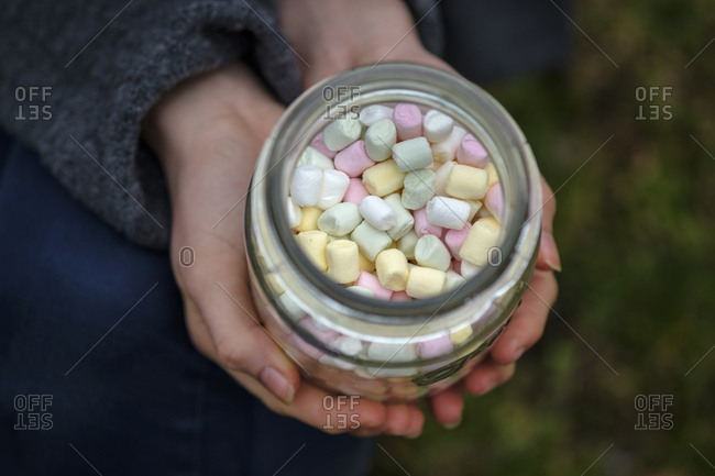 Hands holding glass of marshmallows- close-up