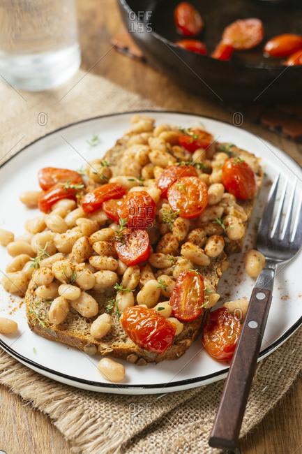 White bean and tomato ragout on toast- white beans- vegetable bouillon powder- Italian herbs- whole grain toast- cherry tomatoes- thyme