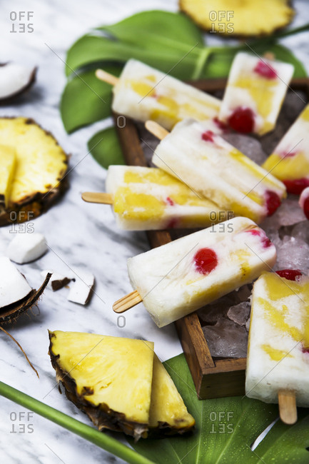 Pina Colada popsicles with candied cherries and pineapple