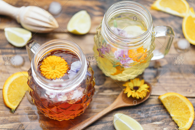 Refreshing mineral water with edible flowers- Viola wittrockiana- Dianthus caryophyllus- Calendula officinalis- lemon and orange
