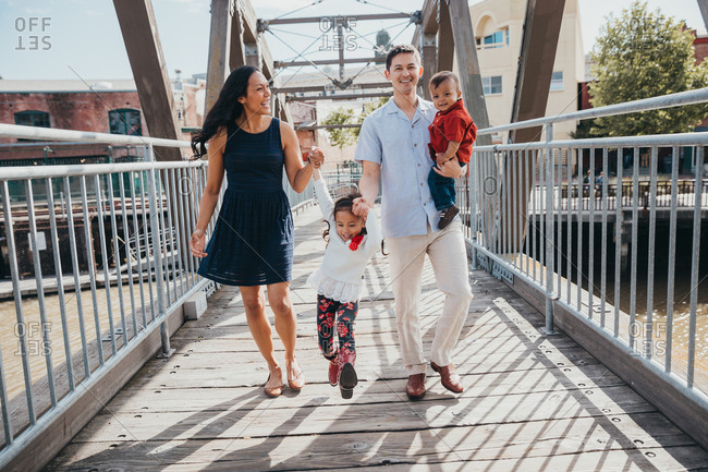 Happy family of four walking on bridge