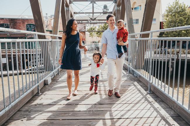 Family of four walking on bridge