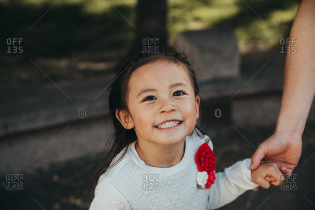 Portrait of a five year old girl holding parent's hand