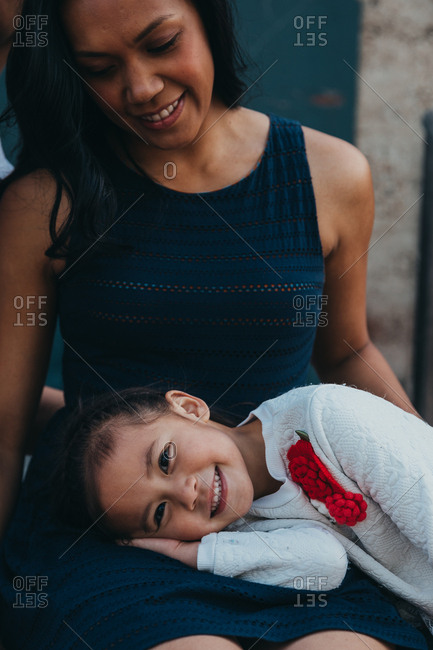 Daughter resting head in mother's lap