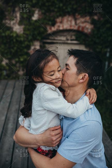 Dad kissing daughter on cheek