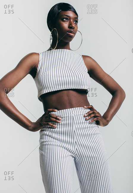 Young model in white pinstripe outfit standing with hands on hips