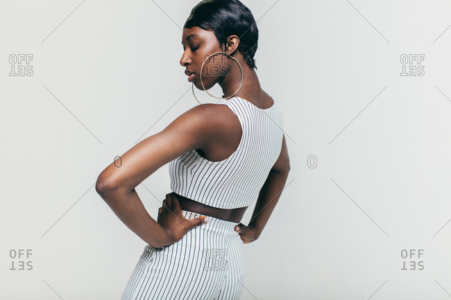 Profile view of young model in white pinstripe outfit standing with hands on hips