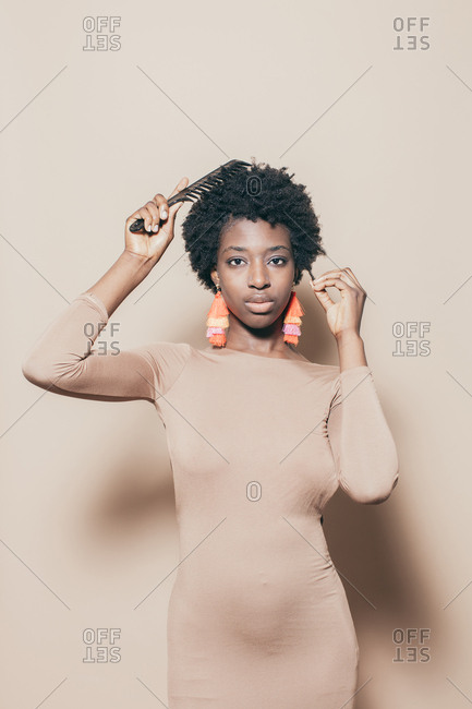 African American woman wearing nude dress and combing her hair