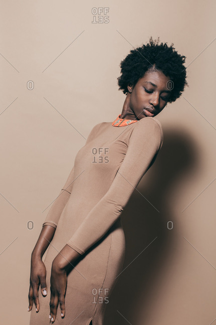 Black woman modeling a nude dress and beaded necklace
