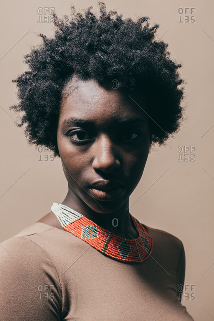 African American woman wearing a nude dress and beaded necklace