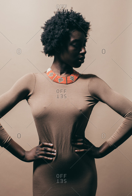Portrait of African American woman wearing nude dress and beaded necklace