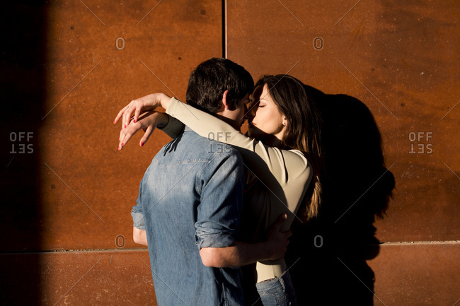 Couple embraces by a wall