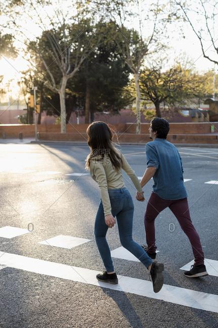 Couple walks hand in hand across city street, Barcelona, Spain