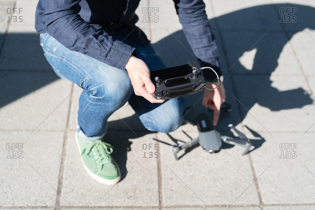 Man holding controller crouching next to miniature drone