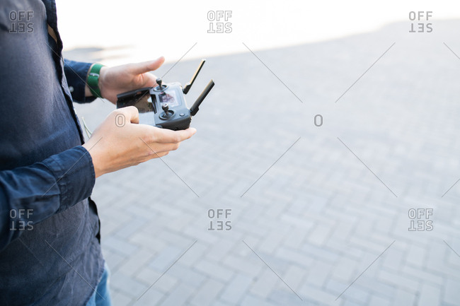 Side view of man's hands holding drone controller